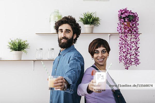 Porträt eines Paares mit Gläsern verschiedener Smoothies fertig zum Trinken