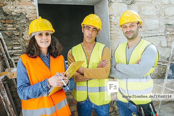 Frau mit zwei Bauarbeitern auf der Baustelle