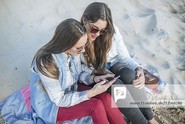 Zwei junge Frauen sitzen am Strand und schauen auf das Handy.