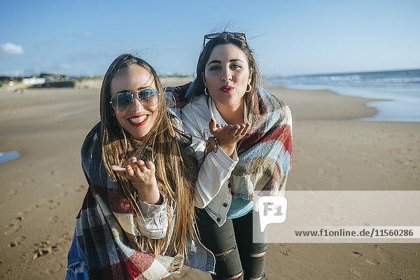 Porträt von zwei jungen Frauen am Strand  die Küsse blasen