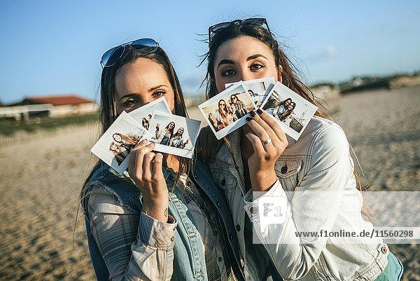 Zwei junge Frauen  die Sofortbilder vor ihren Gesichtern halten.