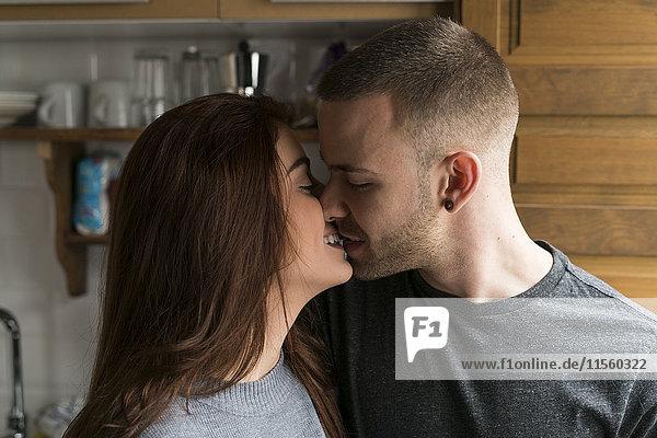 Junges Paar  das sich zu Hause küsst