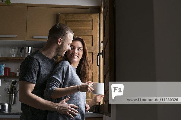 Liebespaar steht in der Küche und umarmt sich mit einer Tasse Kaffee.