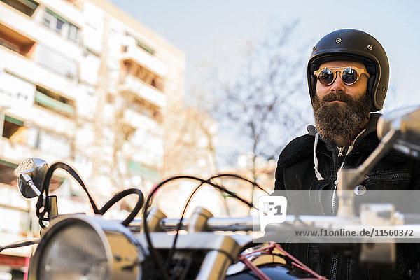 Porträt eines bärtigen Bikers mit Helm und Sonnenbrille auf dem Motorrad