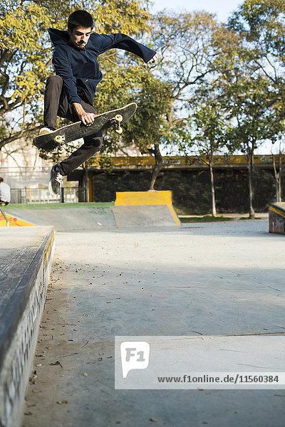 Junger Mann beim Skateboardfahren im Skatepark