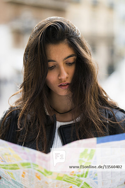 Young woman looking in city map