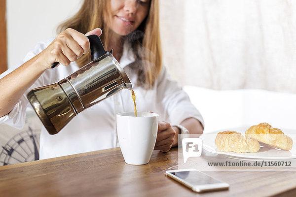 Frau am Frühstückstisch gießt Kaffee in die Tasse