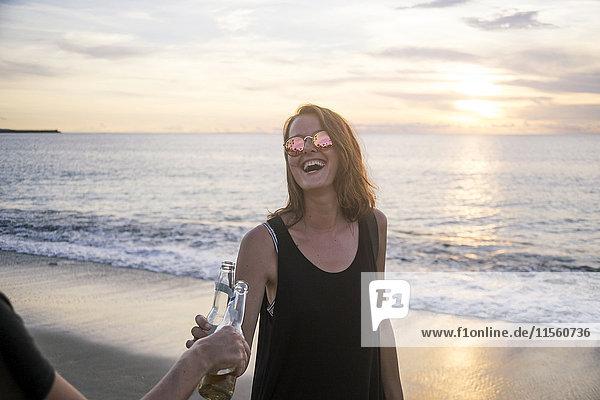 Indonesien  Bali  glückliche Frau klirrende Bierflasche mit Freund am Strand bei Sonnenuntergang