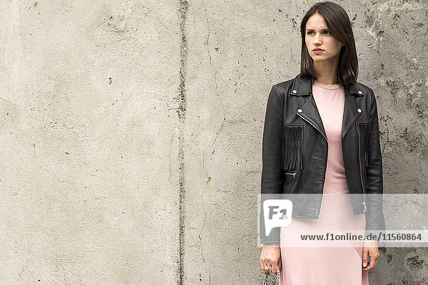 Portrait of young woman wearing black leather jacket and pink dress in front of concrete wall