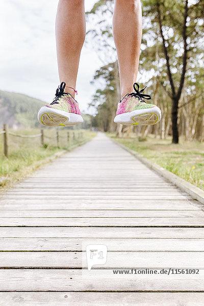 Beine eines Athleten beim Springen auf der Promenade