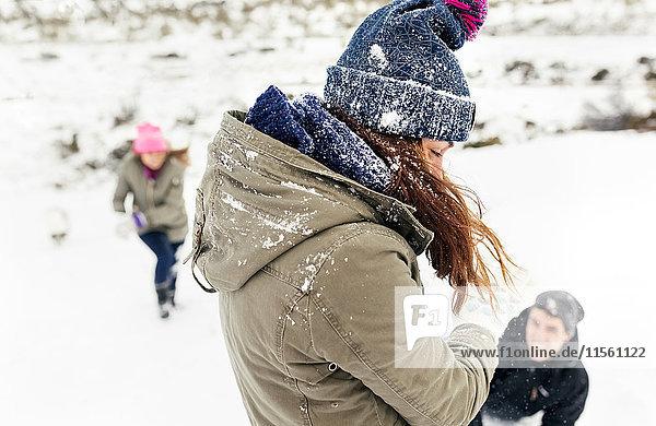 Freunde bei einer Schneeballschlacht im Schnee