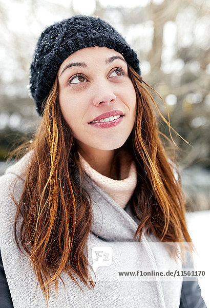 Young woman outdoors in winter looking up
