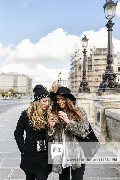 Frankreich  Paris  zwei weibliche Touristen  die in der Stadt spazieren gehen und das Handy anschauen.