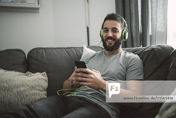 Junger Mann sitzt auf dem Sofa und hört Musik von seinem Smartphone.