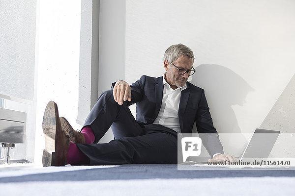 Businessman sitting on the floor using laptop