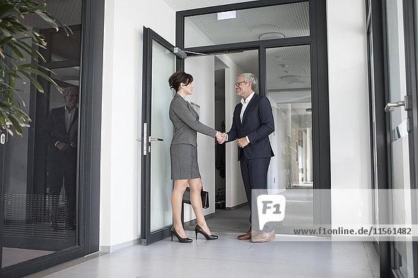 Geschäftsmann und Geschäftsfrau beim Händeschütteln im Büroflur
