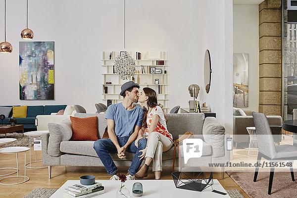 Paar im modernen Möbelhaus auf der Couch sitzend  küssend Paar im modernen Möbelhaus auf der Couch sitzend, küssend