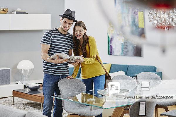 Paar im Möbelhaus mit Blick auf Esstisch  Blick auf Katalog Paar im Möbelhaus mit Blick auf Esstisch, Blick auf Katalog
