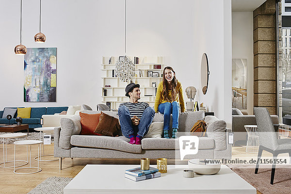 Paar im modernen Möbelhaus auf der Couch sitzend  lachend Paar im modernen Möbelhaus auf der Couch sitzend, lachend