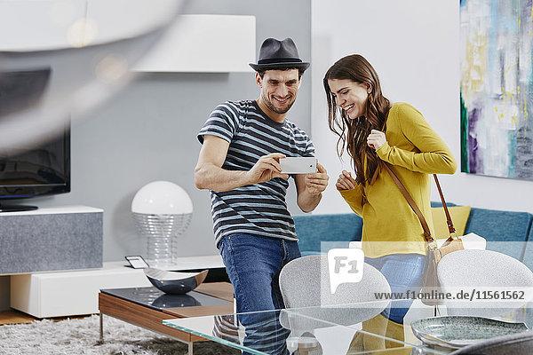 Paar im Möbelhaus mit Blick auf den Esstisch  Fotografieren mit Smartphone Paar im Möbelhaus mit Blick auf den Esstisch, Fotografieren mit Smartphone