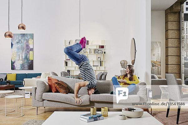 Paar im modernen Möbelhaus mit Kopfstand auf der Couch