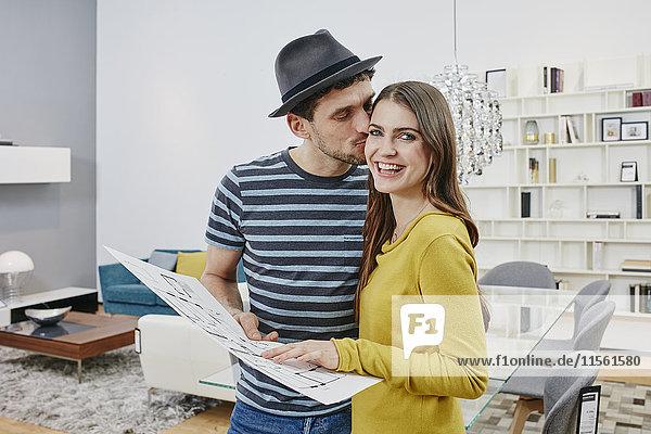 Paar mit Grundriss Auswahl der Möbel im Möbelgeschäft Paar mit Grundriss Auswahl der Möbel im Möbelgeschäft