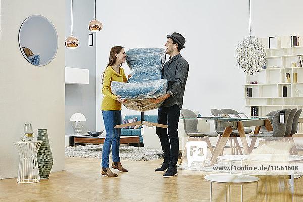 Glückliches Paar mit neuem Sessel aus dem Möbelhaus Glückliches Paar mit neuem Sessel aus dem Möbelhaus