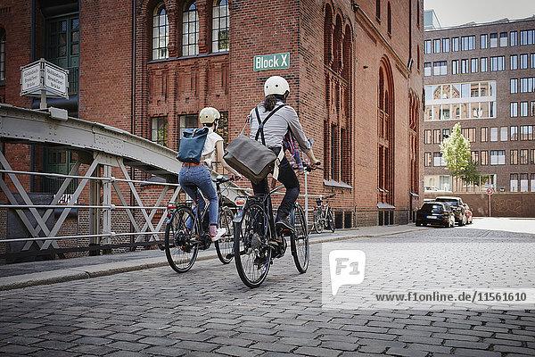 Deutschland  Hamburg  Rückansicht des Ehepaares auf Elektrofahrrädern im Alten Speicherstadtteil