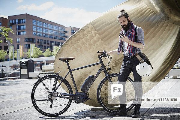 Mann mit Elektrofahrrad beim Blick auf sein Handy