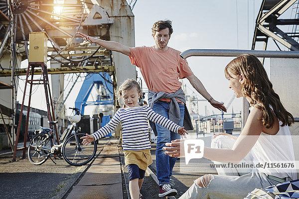 Deutschland  Hamburg  Vater und Tochter balancieren auf der Schiene am Hafen