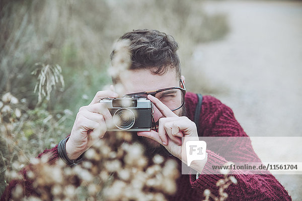 Bearded man taking photo of flowers with vintage camera