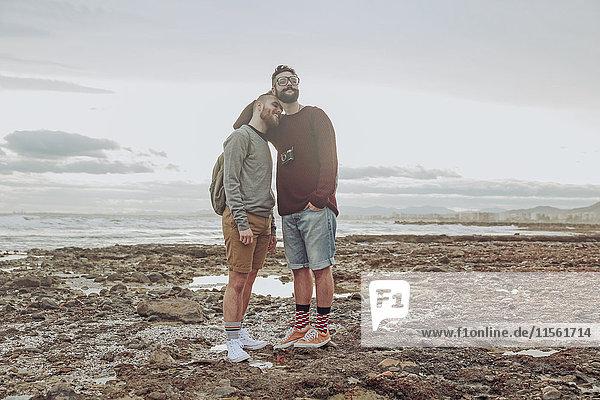 Fröhliches junges schwules Paar am Strand stehend