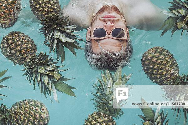 Junger Mann im Schwimmbad umgeben von Ananas
