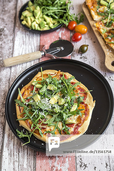 Vegetarian pizza with avocado  rocket  tomatoes and parmesan on plate