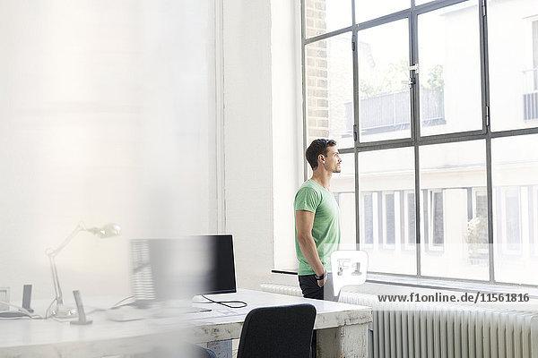 Junger Geschäftsmann schaut aus dem Bürofenster  sieht nachdenklich aus.