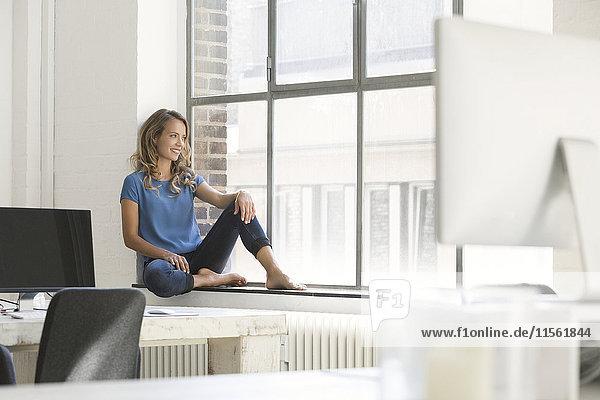 Lässige Geschäftsfrau im Büro  auf der Fensterbank sitzend