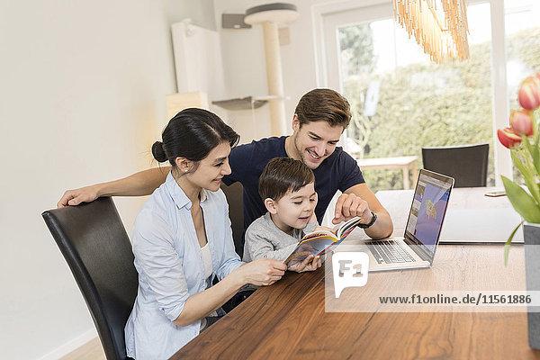 Familie mit Laptop und Reiseführer bei der Urlaubsplanung zu Hause