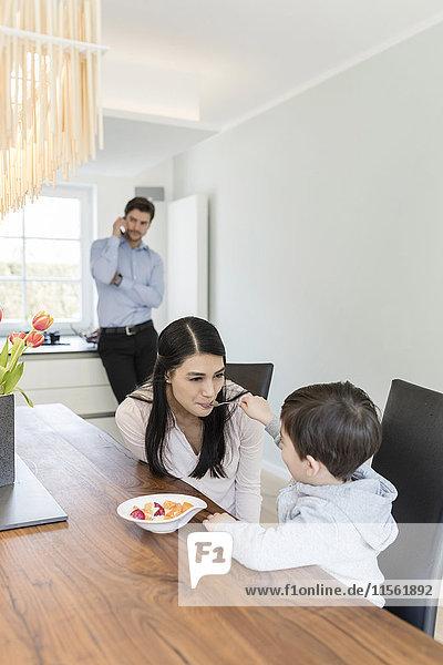 Mutter und Sohn beim Frühstück mit Vater am Telefon im Hintergrund