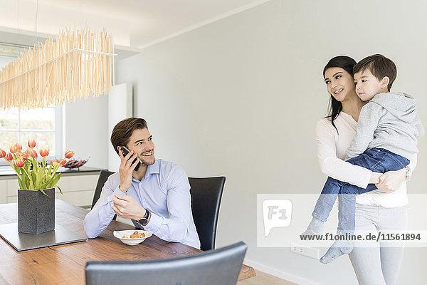 Mutter mit Sohn und Vater am Telefon beim Frühstücken
