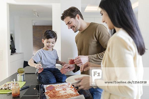Familie bereitet gemeinsam Pizza in der Küche zu