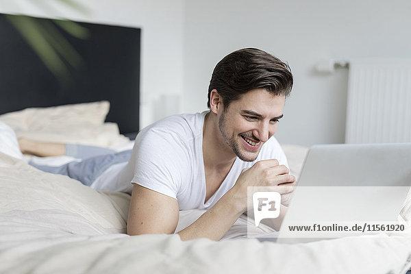 Lächelnder Mann auf dem Bett liegend mit Laptop