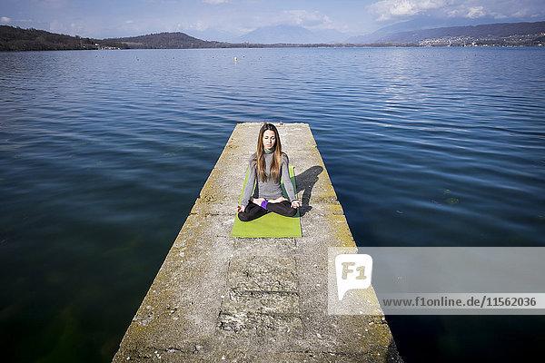 Frau praktiziert Yoga auf einem Pier am See Frau praktiziert Yoga auf einem Pier am See