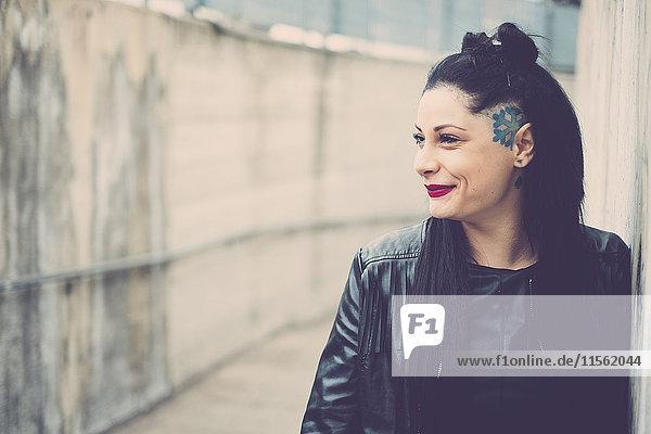 Lächelnde dunkelhaarige junge Frau mit schwarzer Lederjacke und Tattoos