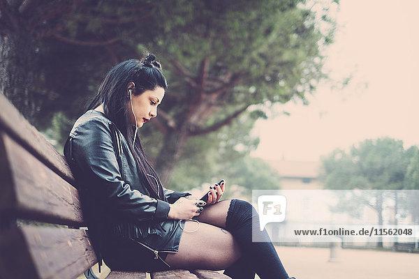 Dunkelhaarige junge Frau sitzt auf der Bank und hört Musik mit Kopfhörern und Smartphone. Dunkelhaarige junge Frau sitzt auf der Bank und hört Musik mit Kopfhörern und Smartphone.
