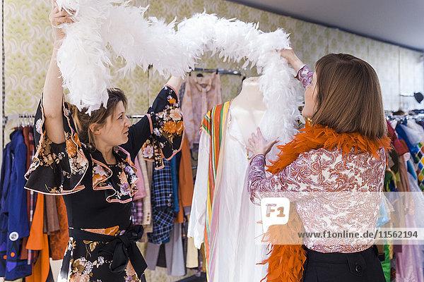 Zwei Frauen mit Federboa in einem Second-Hand-Laden