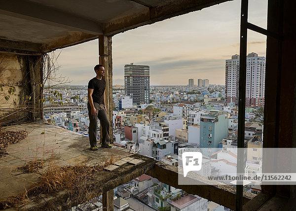 Vietnam  Ho-Chi-Minh-Stadt  Mann steht in Ruine eines Wolkenkratzers