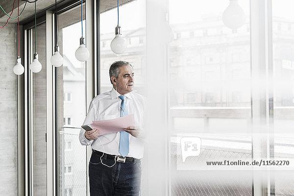 Senior Manager im Büro stehend am Fenster sprechend auf Smartphone  haltend Dokument