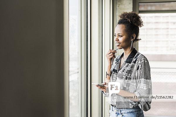 Junge Frau am Fenster stehend mit dem Smartphone