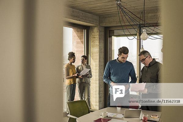 Geschäftsmann zeigt Dokument dem Kollegen im Büro