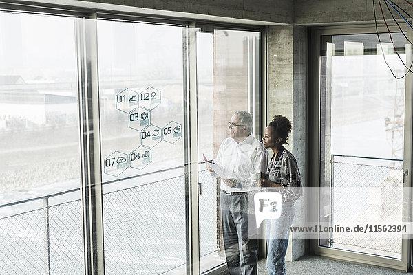 Geschäftsmann und Frau an der Fensterscheibe mit Daten im Büro
